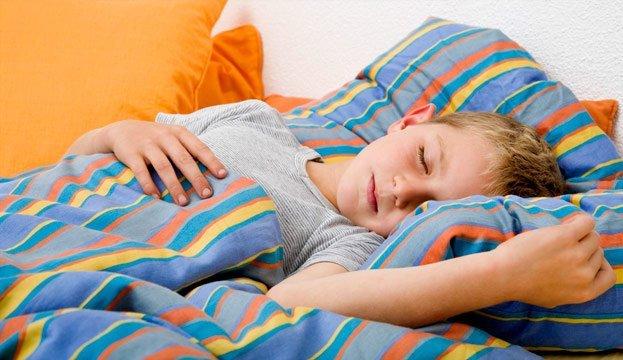 Мальчик спит в кровати