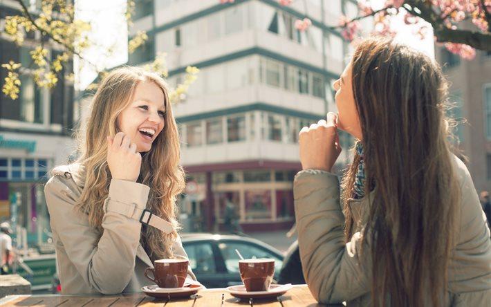 Две девушки беседуют в уличном кафе