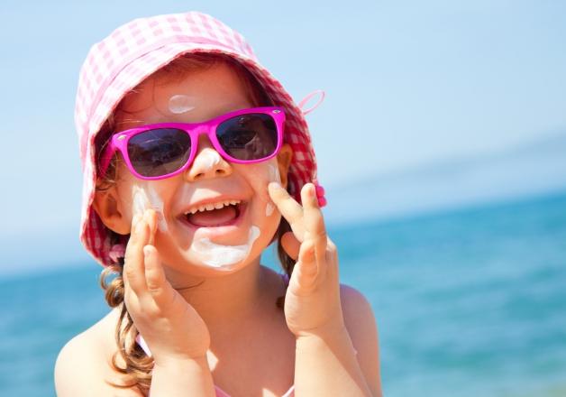 Девочка в панаме и солнцезащитных очках наносит на лицо крем