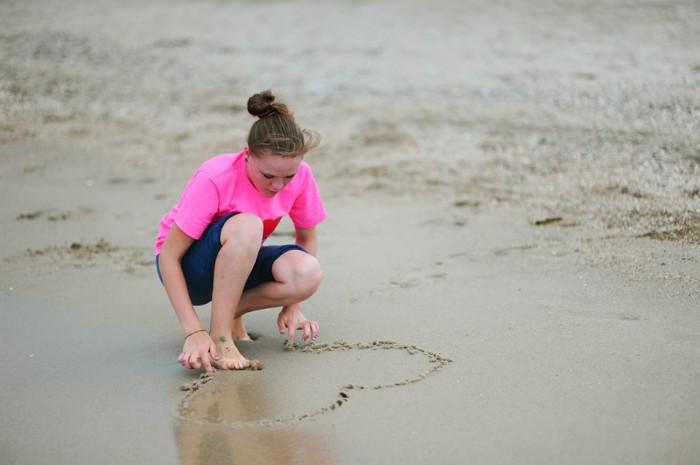 Девочка-подросток рисует сердце на песке пляжа