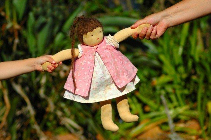 Куклу растягивают за руки в разные стороны