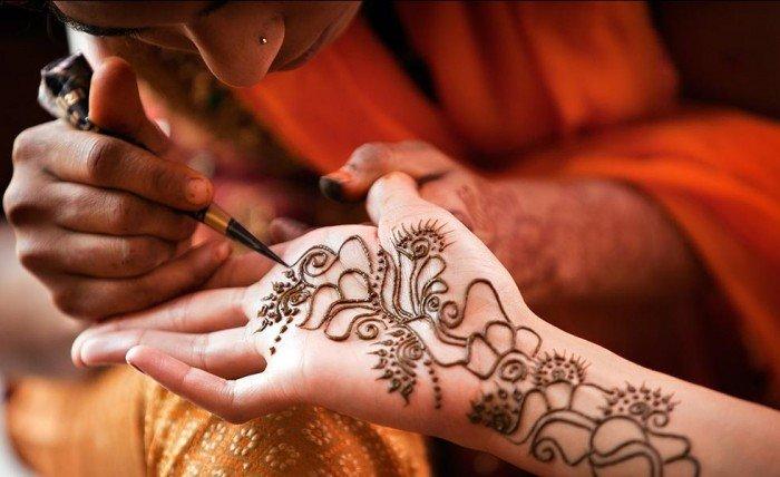 Мастер рисует на руке