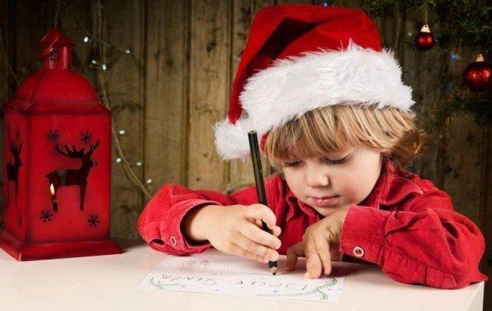 Мальчик в красной шапке пишет письмо