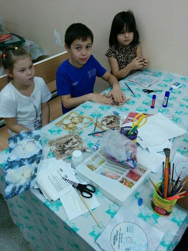 Трое детей за столом делают поделки