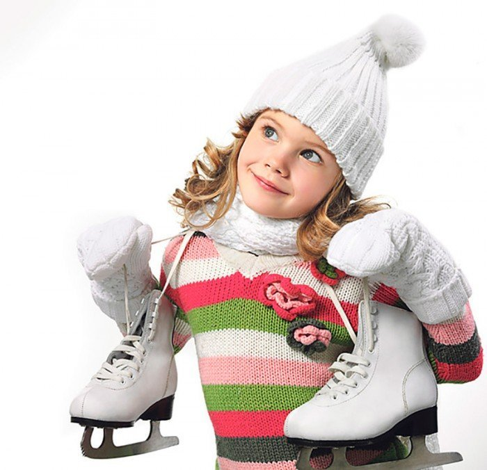 Девочка в белой шапке с коньками на шее