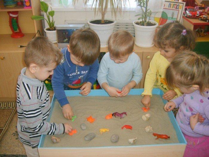 Дети играют в псеке несколькими фигурками и камешками