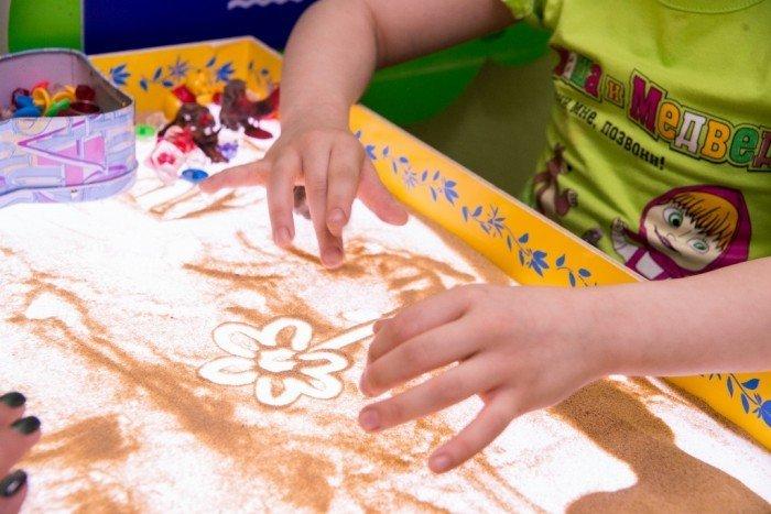 Ребёнок рисует цветок на песке