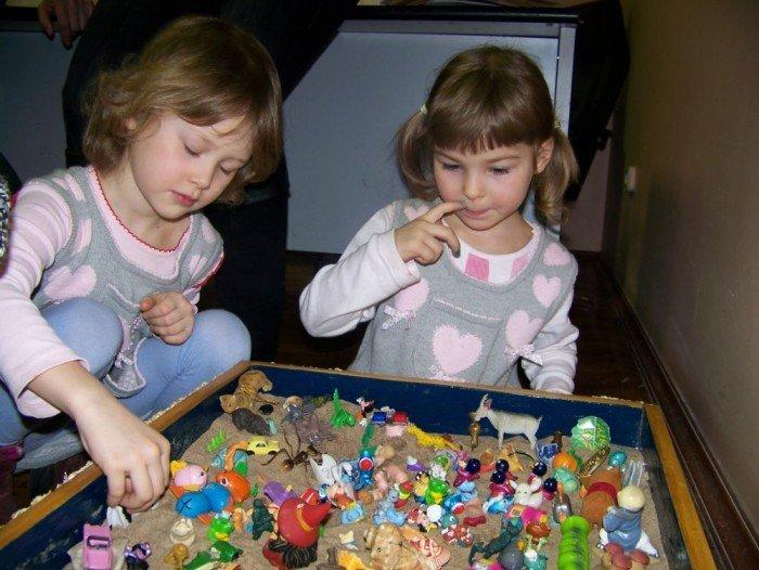Девочки и много фигурок в ящике с песком