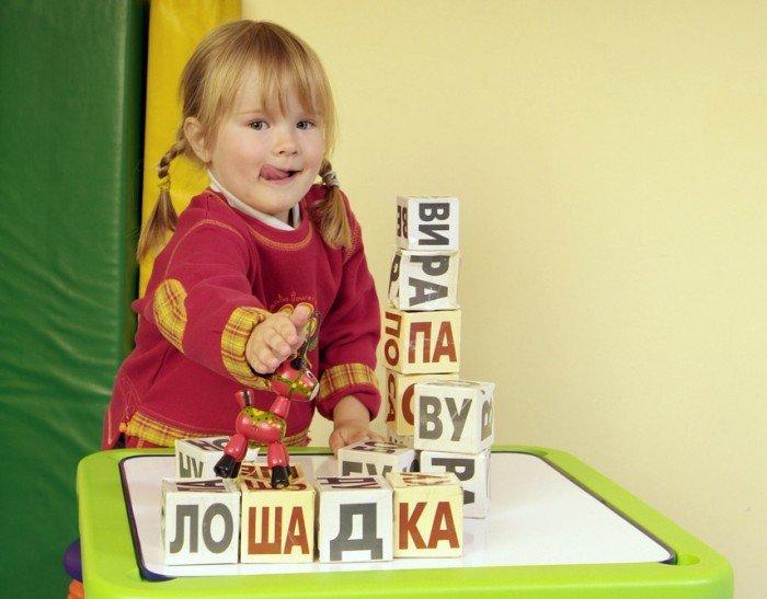 Девочка с косичками и кубики со словом «лошадка»
