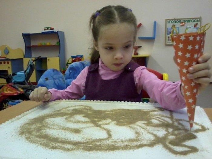 Девочка пересыпает песок