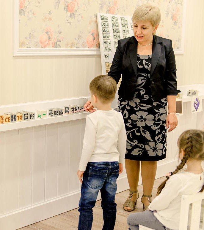 Учитель показывает мальчику склад на кубиках