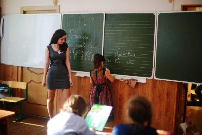 Девочка-учитель проверяет на доске слова, написанные по слогам
