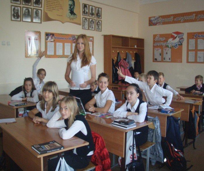 Девочка-учитель стоит, ученики среднего звена тянут руки отвечать