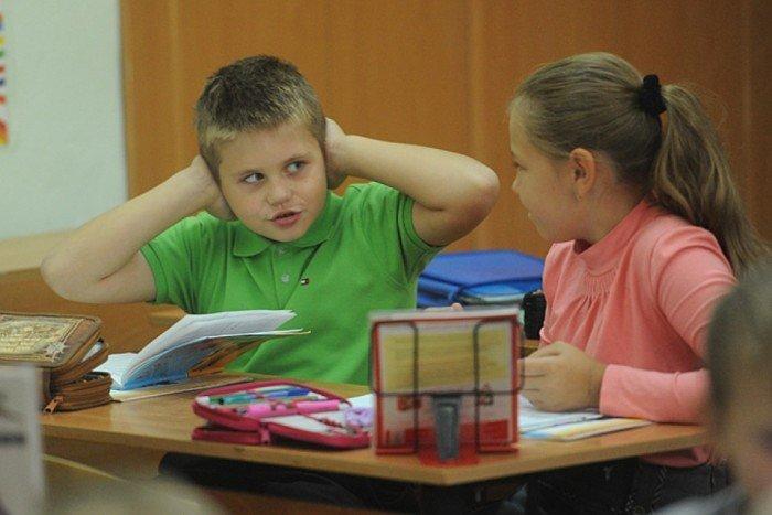 Мальчик в зелёной футболке закрыл уши и читает девочке вслух