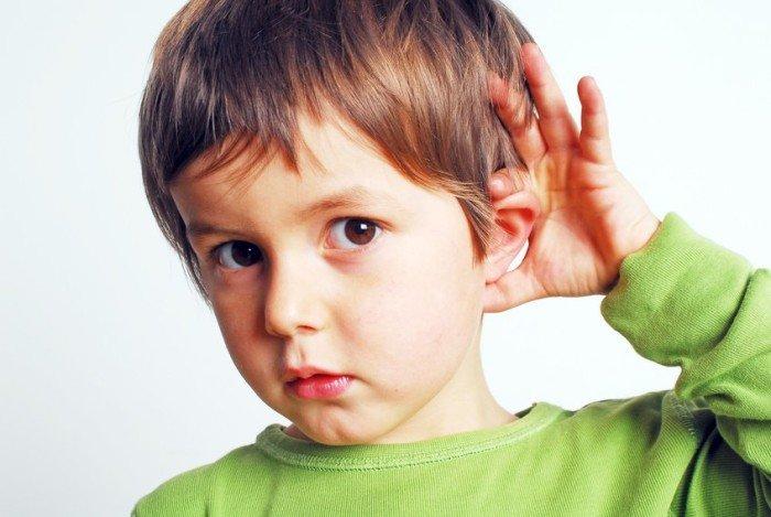 Мальчик в зелёной кофте держит себя за ухо