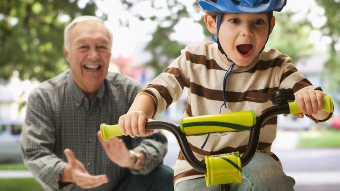 Дедушка и внук, катающийся на велосипеде