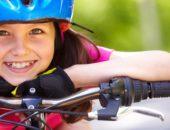 Девочка опирается на руль велосипеда