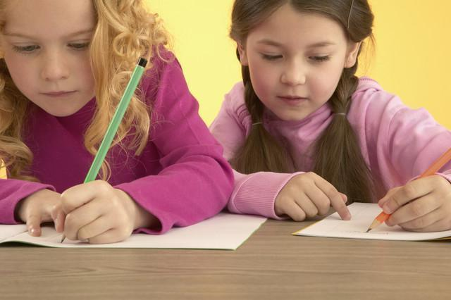 Две девочки пишут
