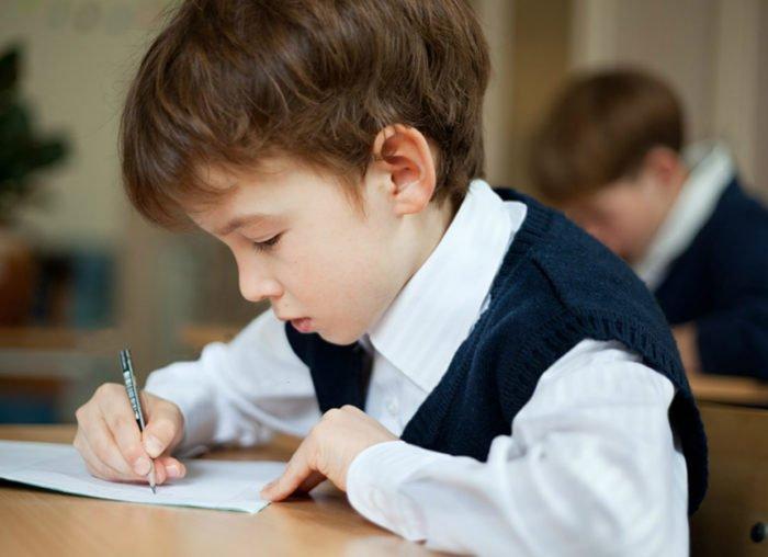 Пишущий мальчик на уроке