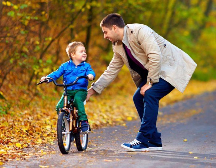 Мужчинаучит мальчика кататься на велосипеде