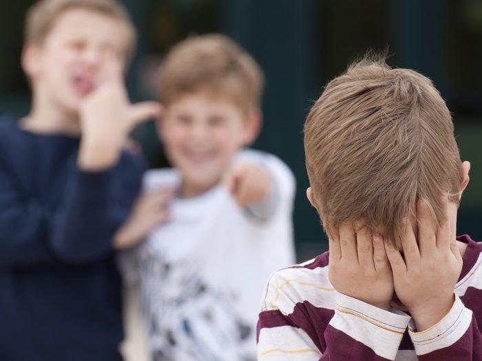 Дети насмехаются над мальчиком