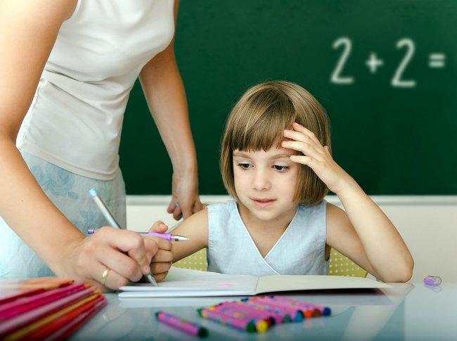 Учительница помогает школьнице