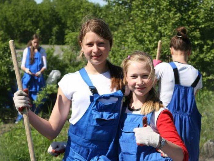 Девочки в синих комбинезонах с лопатами