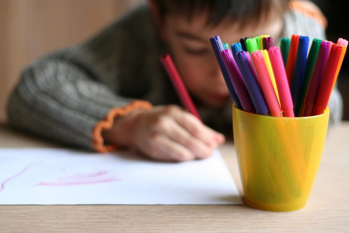 Рисующий мальчик и фломастеры в стакане