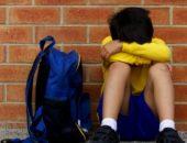 Школьник сидит у стены и плачет