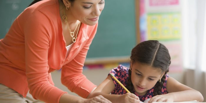 Учитель наблюдает за работой ученицы