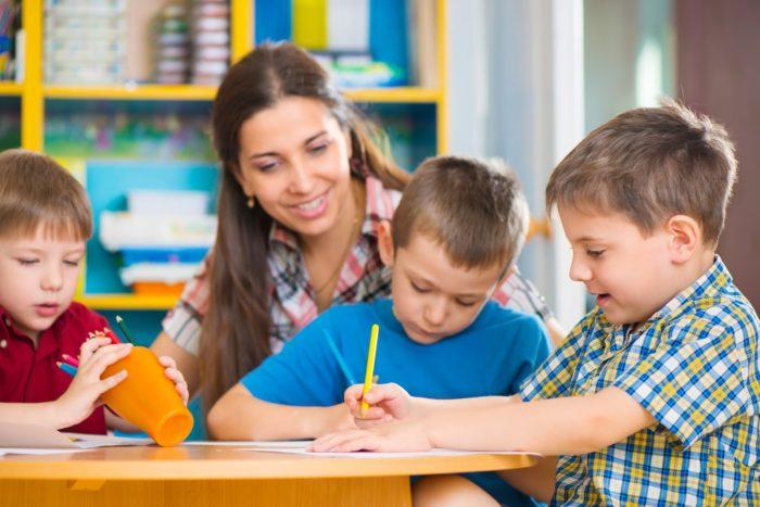 Учитель наблюдает за рисующими детьми