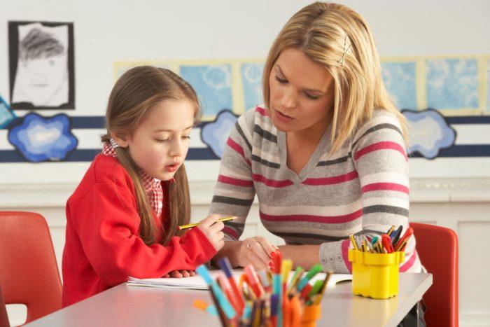 Женщина работает с девочкой над заданием