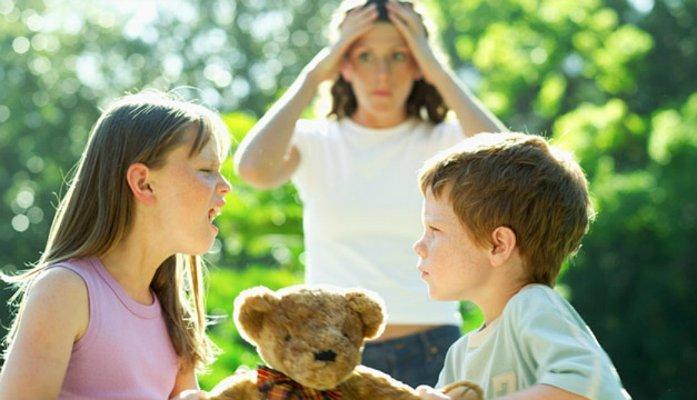 Женщина смотрит, как дети делят игрушку