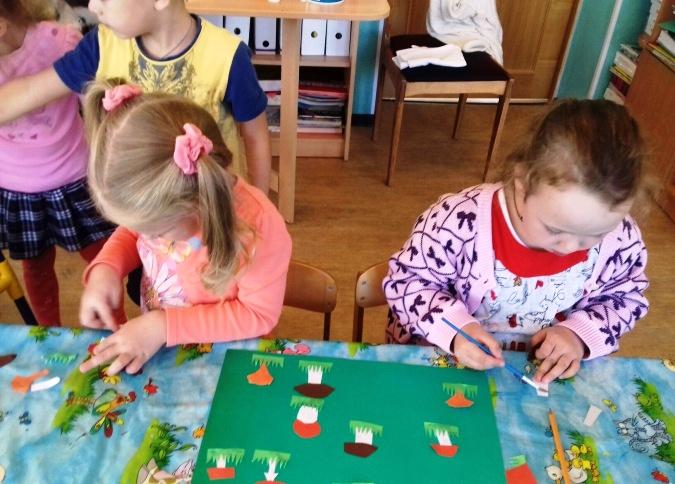 2 девочки клеят грибы на зелёную подложку