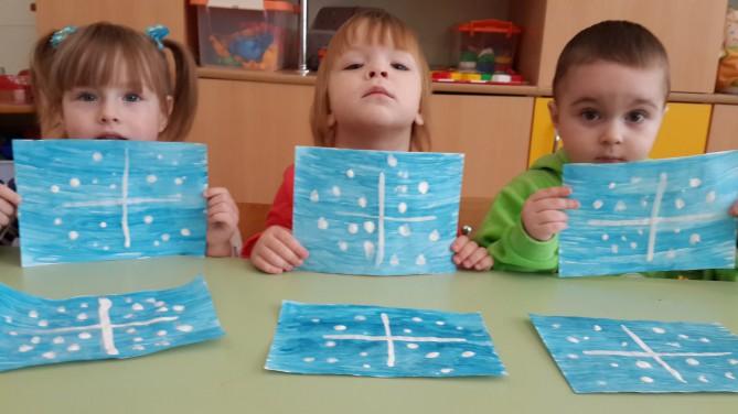 3 детей держат рисунки: снежинки на голубом фоне