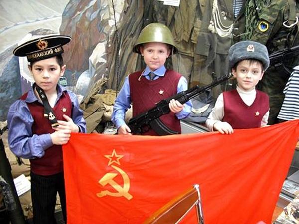 3 мальчика в военных головных уборах с флагом с серпом и молотом