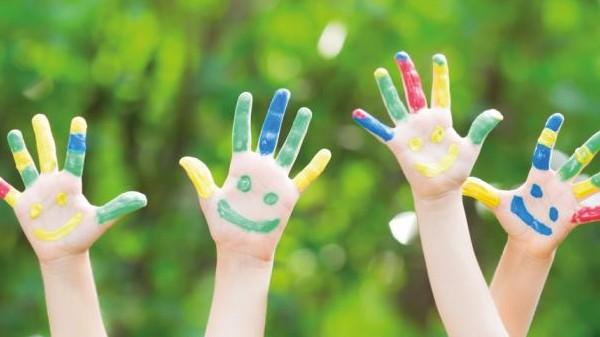 4 ладошки с нарисованными на пальчиках рожицами на фоне зелени