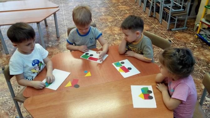 4 малыша выполняют аппликации видов транспорта из геометрических фигур