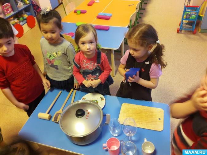 5 детей стоят вокруг столика с посудой