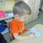 Мальчик ставит точки на шаблон чашки с блюдцем