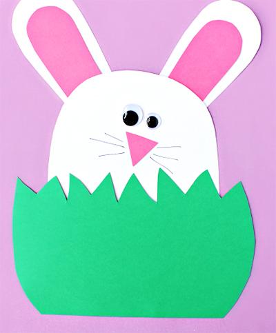 Белый заяц с розовыми ушами в траве