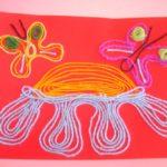 Черепаха нитками на красном листе