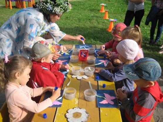 Дети делают на улице за столом поделки-цветочки