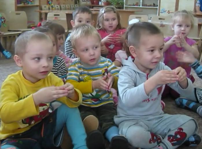 Дети на полу выполняют упражнения пальцами
