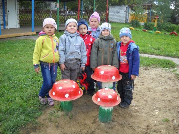 Дети на улице у 3 декоративных мухоморов из тазов