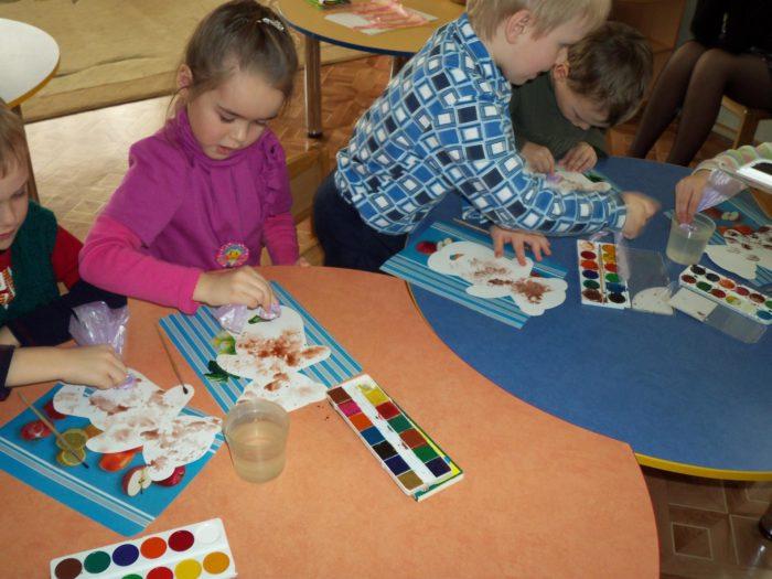 Дети размазывают коричневую краску по шаблону с медведем