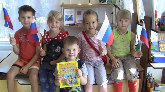 Дети с флажками России и мальчик с книгой о Родине-России на первом плане