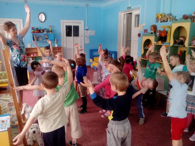 Дети с воспитательницей делают зарядку