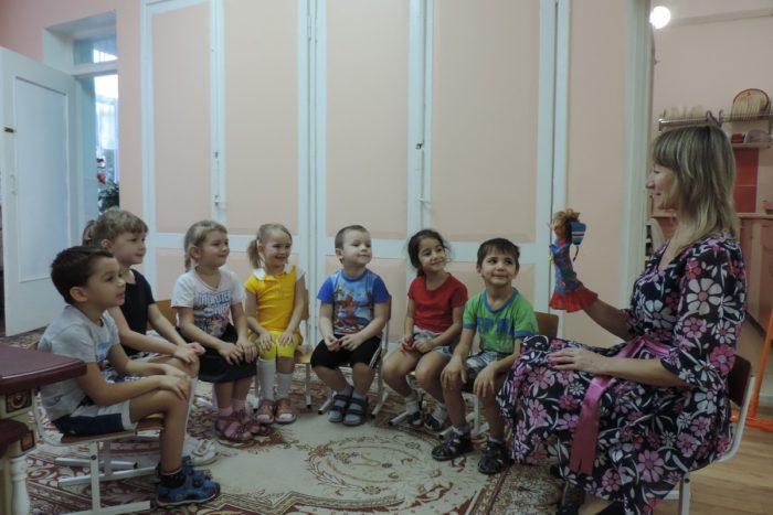 Дети сидят полукругом, воспитательница справа от них