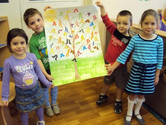 Дети стоят с групповым проектом-нарисованным деревом